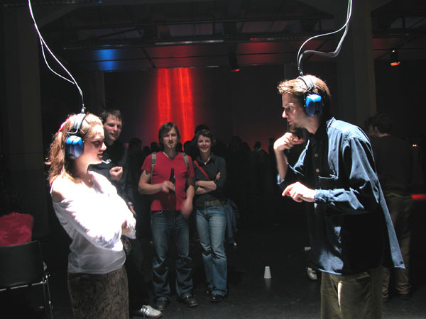 two people stand facing each other, wearing headsets wired to the ceiling, speaking and gesturing to one another  in a museum.
