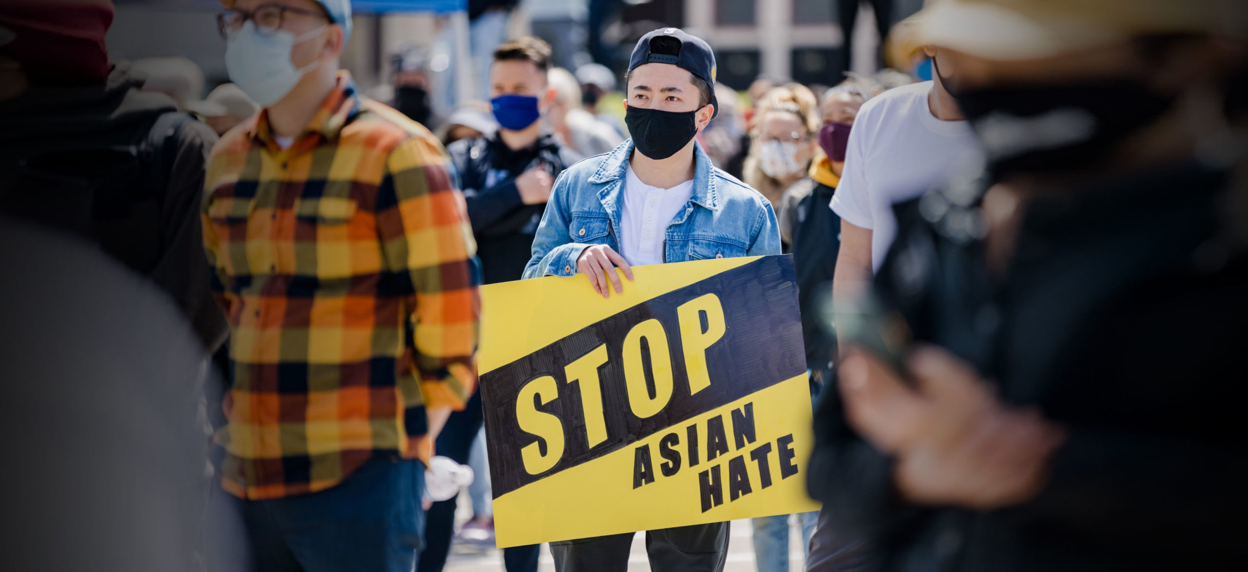 A man holds a #StopAsianHate sign at a large rally