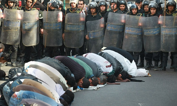 Locals pray in the street in front of The l-Istiqama Mosque watched by riot police in Giza on 28 January 2011 in Cairo, Egypt. Photograph: Peter Macdiarmid/Getty Images