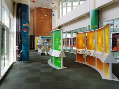 Green and orange curved walls with information panels on them are in the middle of the exhibition. Tall banners cover the pillars at the sides. A bookshelf is in the back.