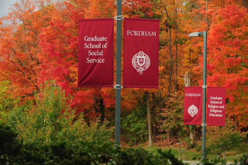 Red banners for Fordham University Graduate School of Social Service line a wooded walkway next to trees during fall
