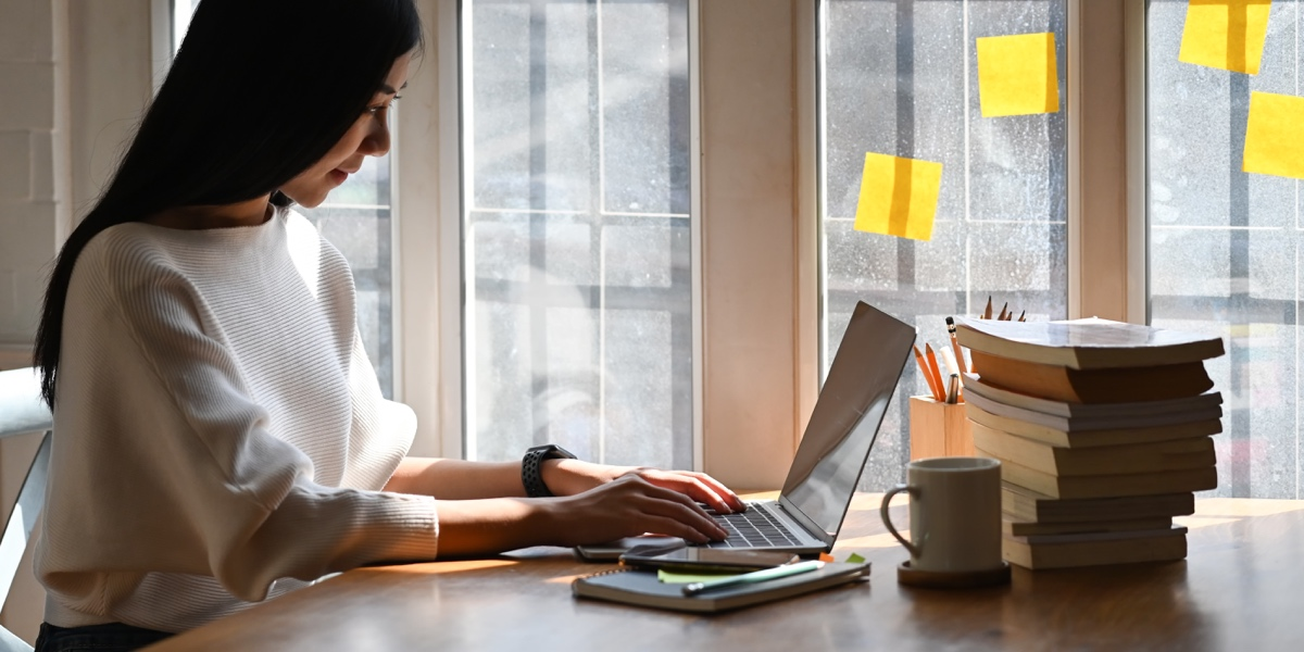 A designer working at a laptop on a desk with a stack of books, near a sunny window covered in sticky notes