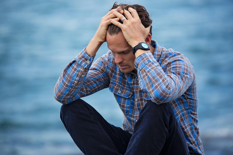 Man running his hands through hair in distress