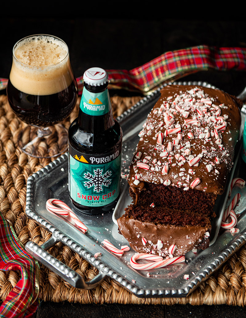 Snow Cap Loaf Cake served with Pyramid's seasonal Snow Cap Winter Ale and garnished with peppermint candy canes, side view - Cooking with beer Winter Ale ingredient in moist Christmas chocolate cake