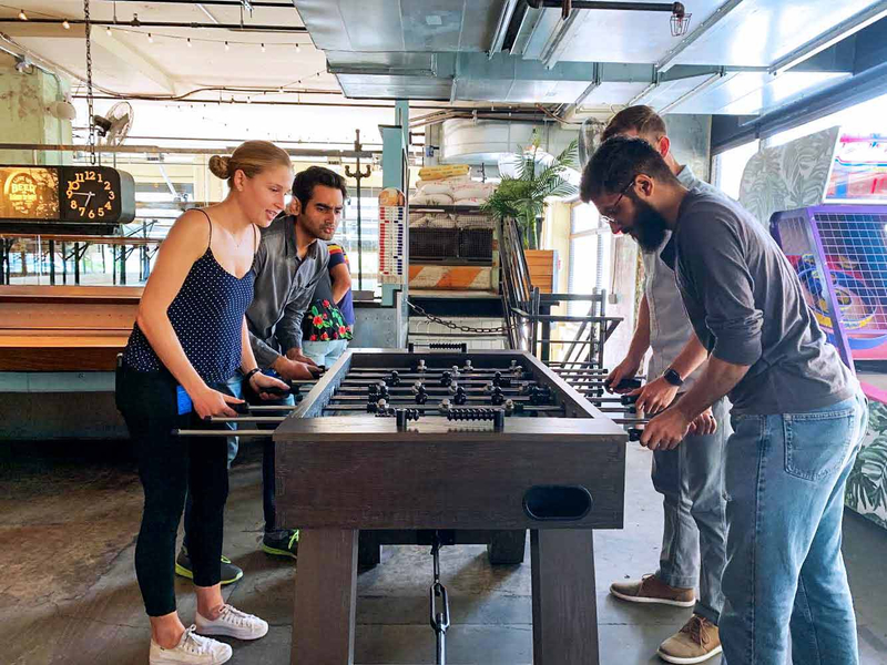 A group of interns unwind after work with a game of foosball