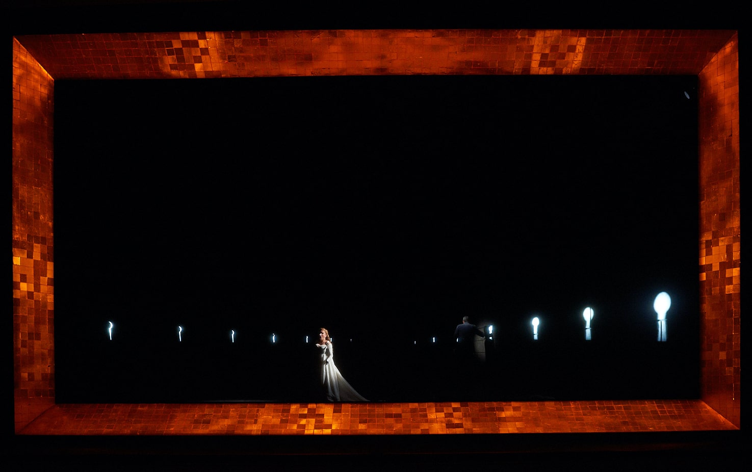 Bride stands in darkened space, flanked by keyhole lights and framed by shimmering amber tile.