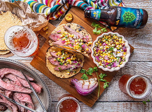Cutting board with Outburst IPA Flank Steak Tacos next to a bottle of Outburst IPA