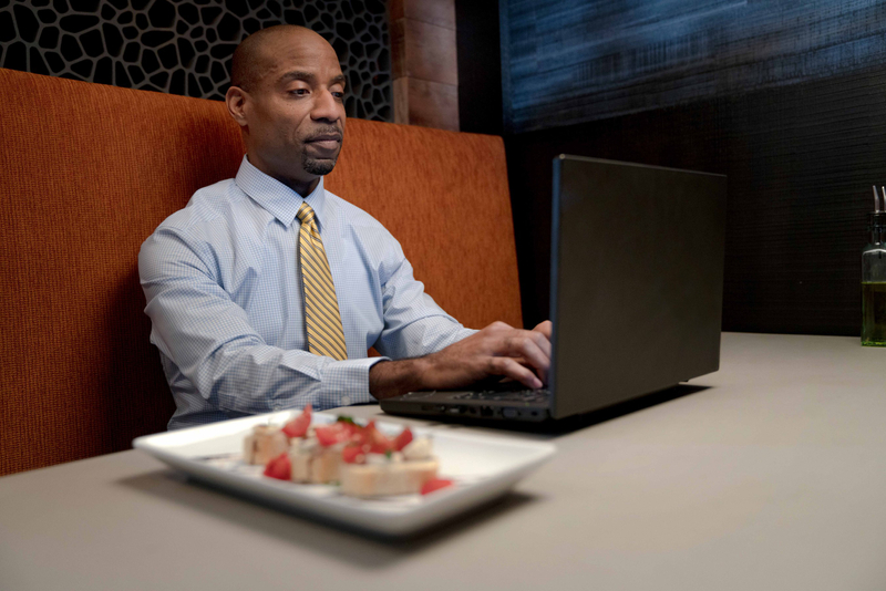Man in a gold striped tie typing on his laptop while sitting in a booth with a plate of food next to him