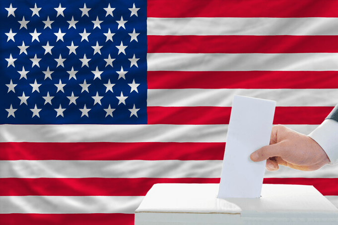 A persons hand casting a ballot with the US flag in the background