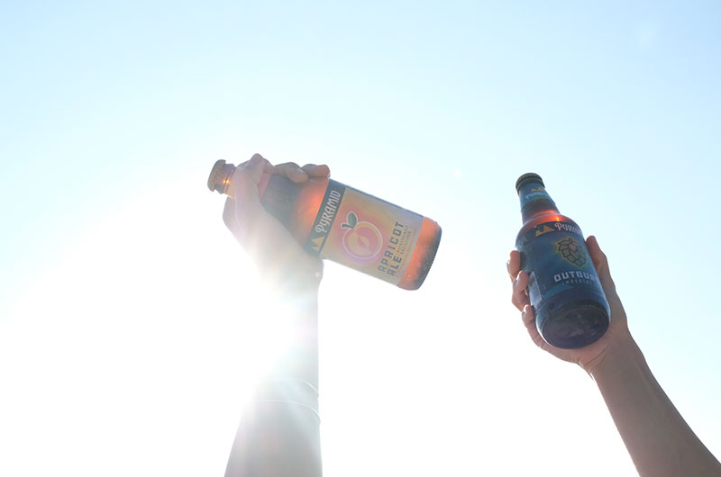 A bottle of Apricot Ale and a bottle of Outburst being help up with the sun in the background