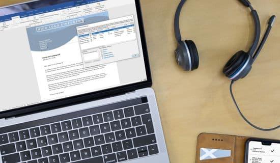 Laptop mit barrierefreiem Word-Dokument und Kopfhörern