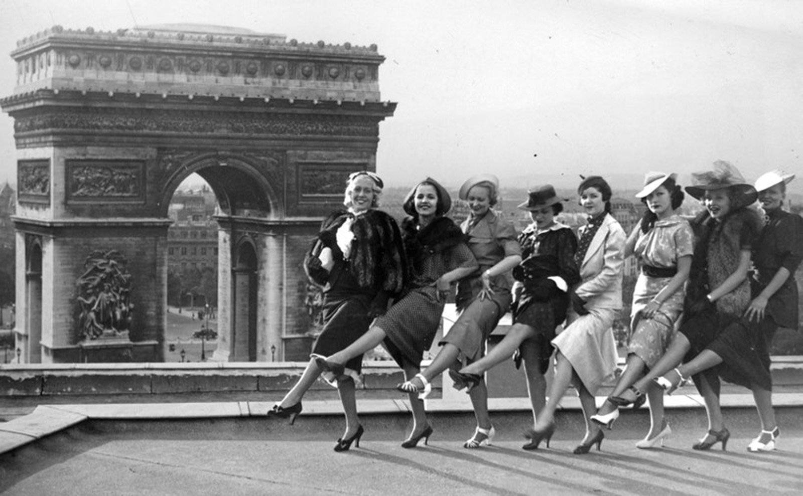 young women posing in front of the arc de triomphe in 1936