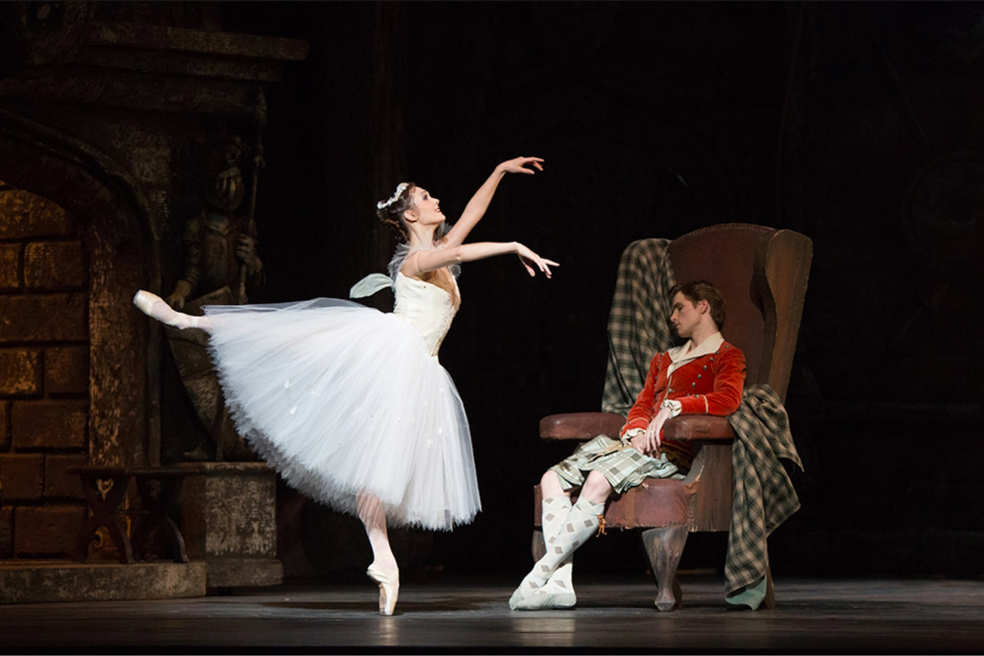 Ballerina in white dress holds graceful arabesque near dancer in kilt and red jacket sleeping in leather armchair.