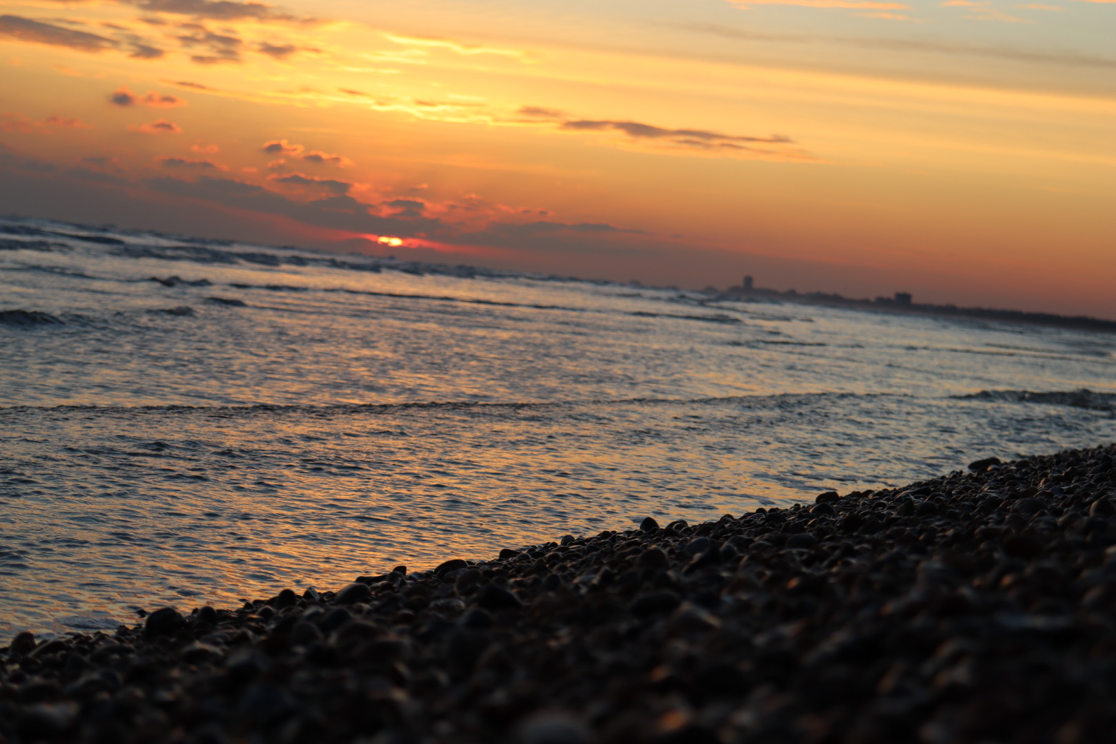 Shingle with little waves breaking behind and a sunset obsured by clouds.
