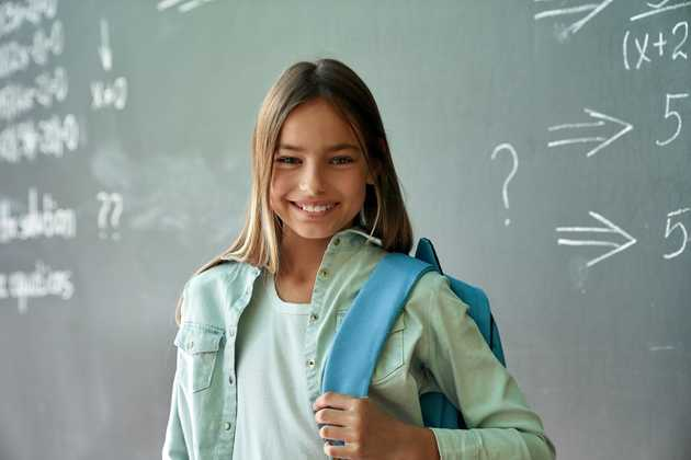 Student smiling in front of blackboard