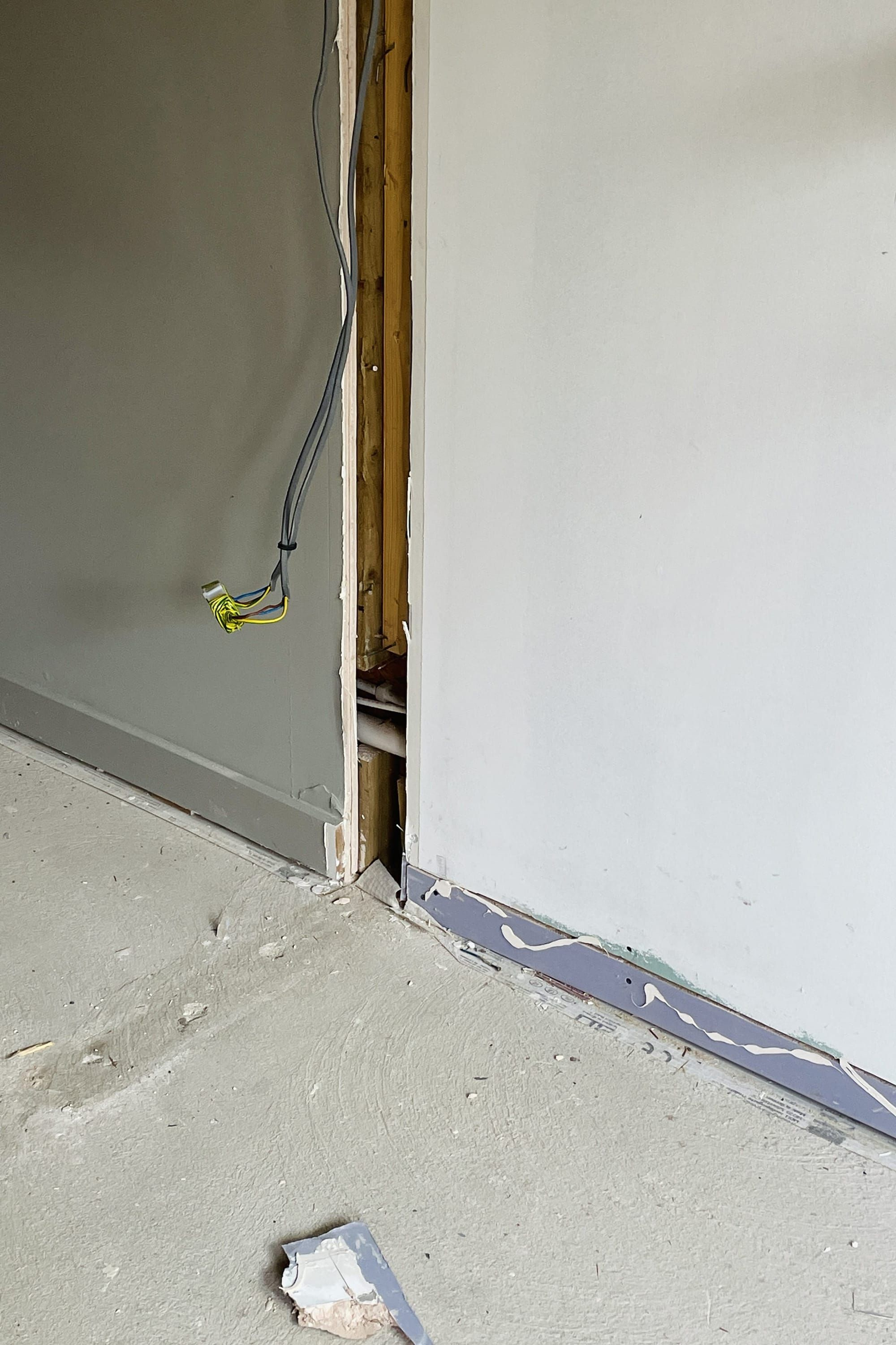 Bare plasterboard walls and exposed concrete floor.