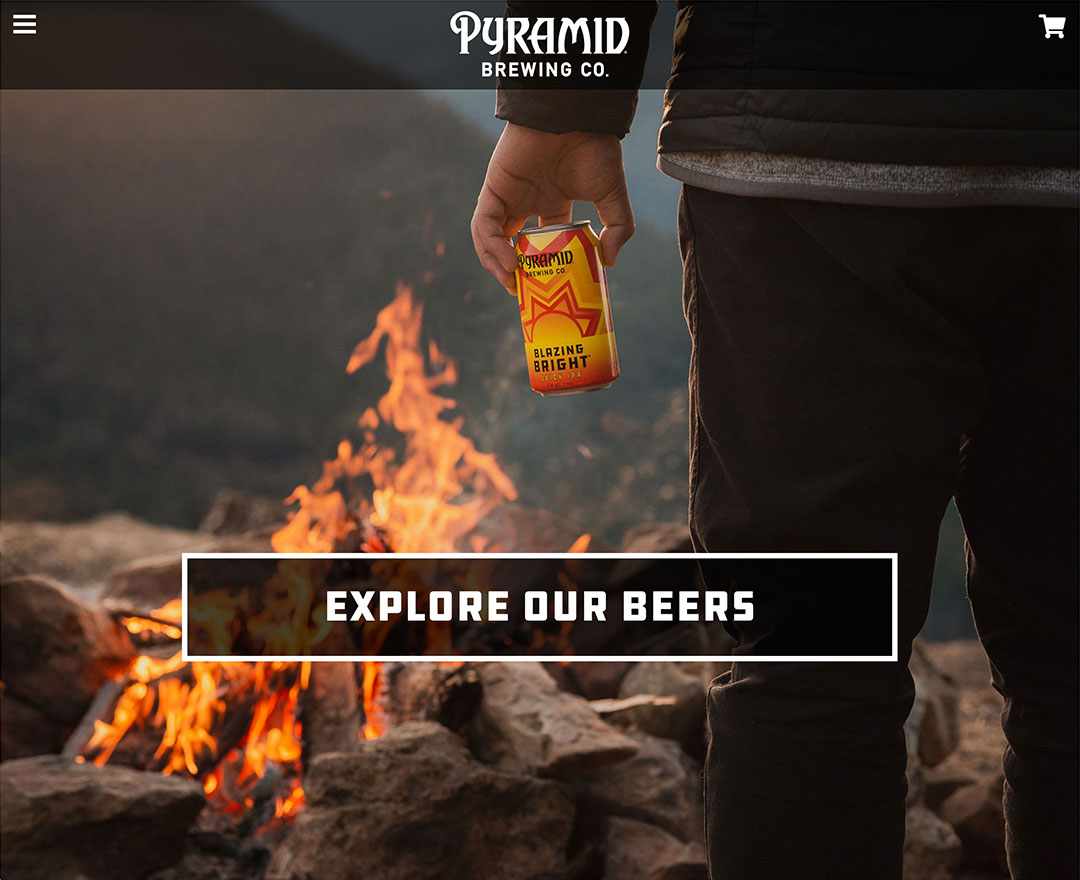 Screenshot of the Pyramid Brewing Co. website with a photo of a man from behind holding a can of beer with a campfire in the background.