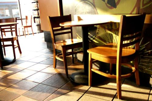 Photo of a coffee shop which is fairly empty, with a few two seater tables freed up, from soopahtoe of FreeImages.com