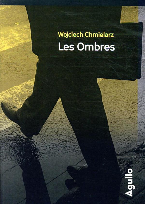 Haut de la couverture jaune qui s'estompe peu à peu pour devenir gris foncé. Les jambes et le bas du manteau d'un homme, portant une mallette, traverse un passage piéton. Nom de l'auteur en jaune en haut, petits caractères, titre en blanc en dessous.