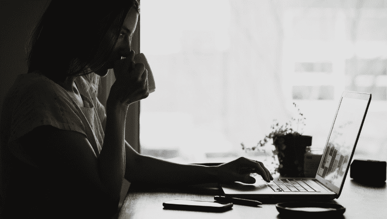 A woman in a shadow drinking a coffee while working on a MacBook laptop next to a window.