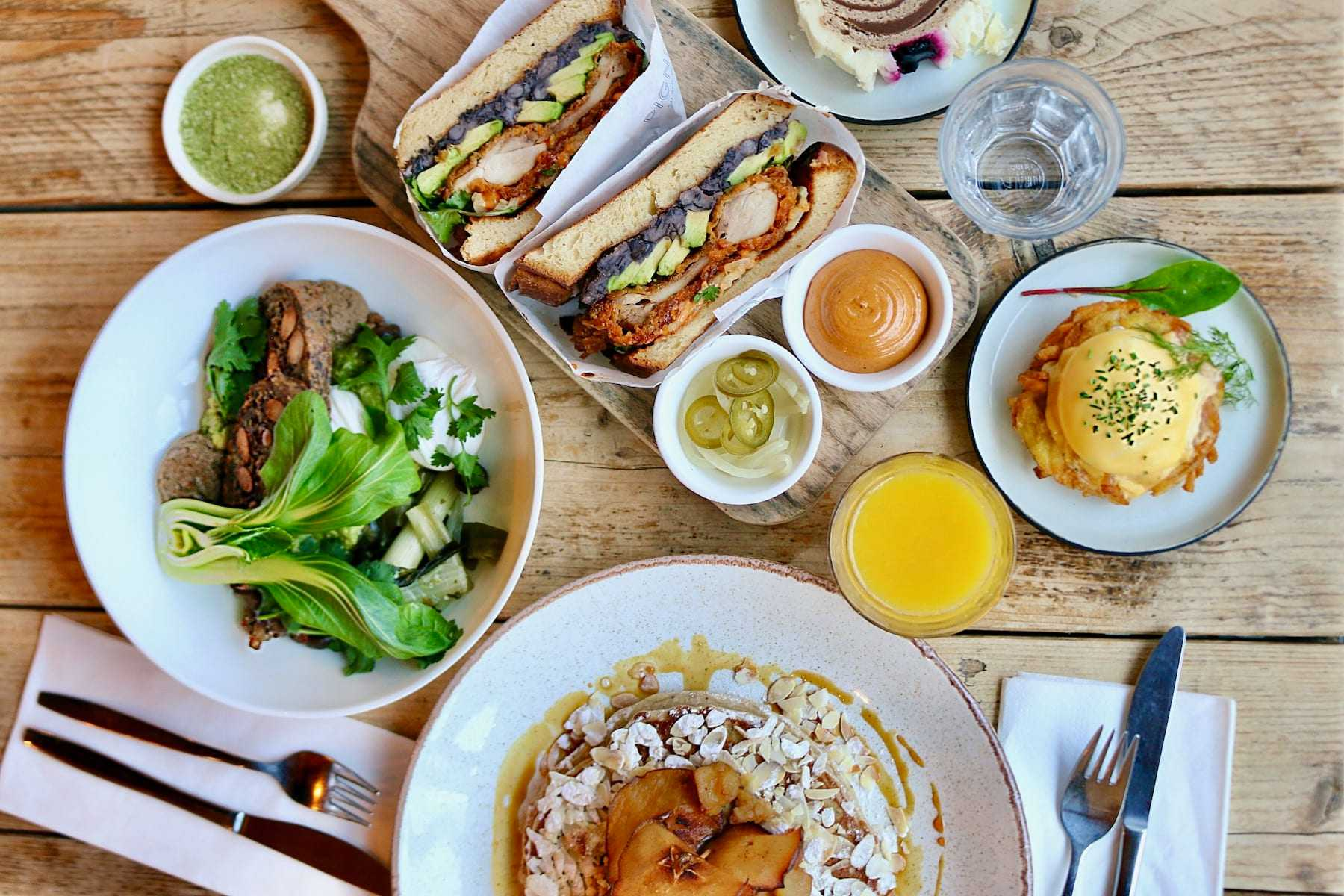 Appetizing Amsterdam brunch dishes: vegetarian bowl, chicken sandwiches, poached eggs on hash browns, pancakes