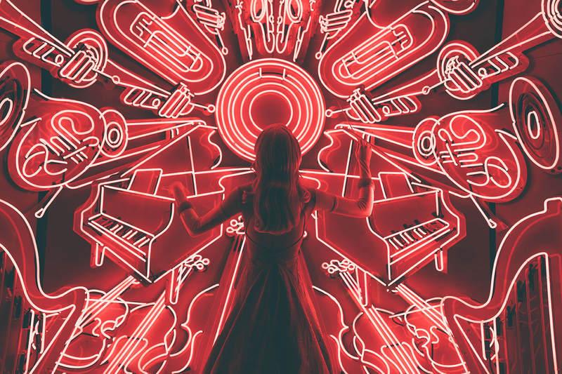 Uma garota de costas, olhando para uma parede cheia de LEDs em formatos de instrumentos musicais.