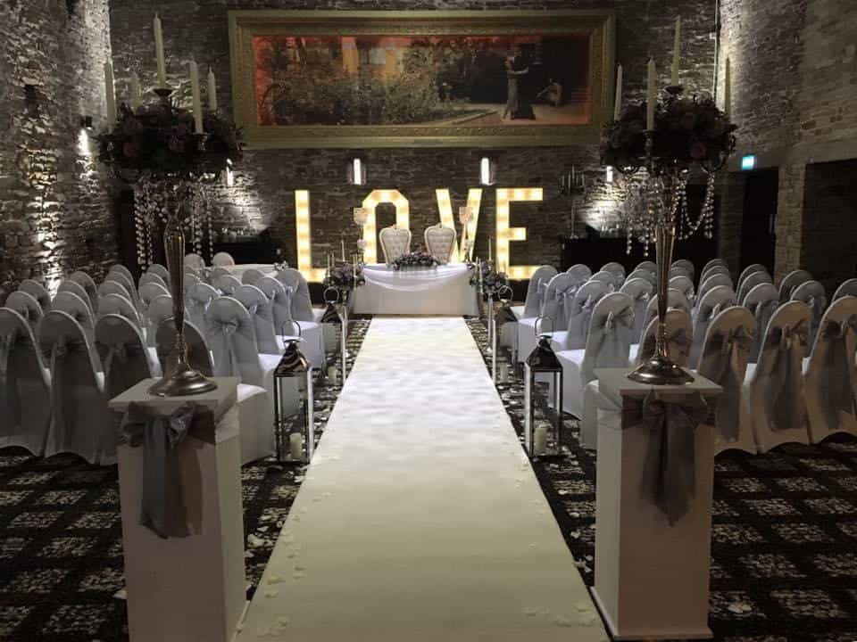wedding ceremony with white chair covers, white runner and giant love letters
