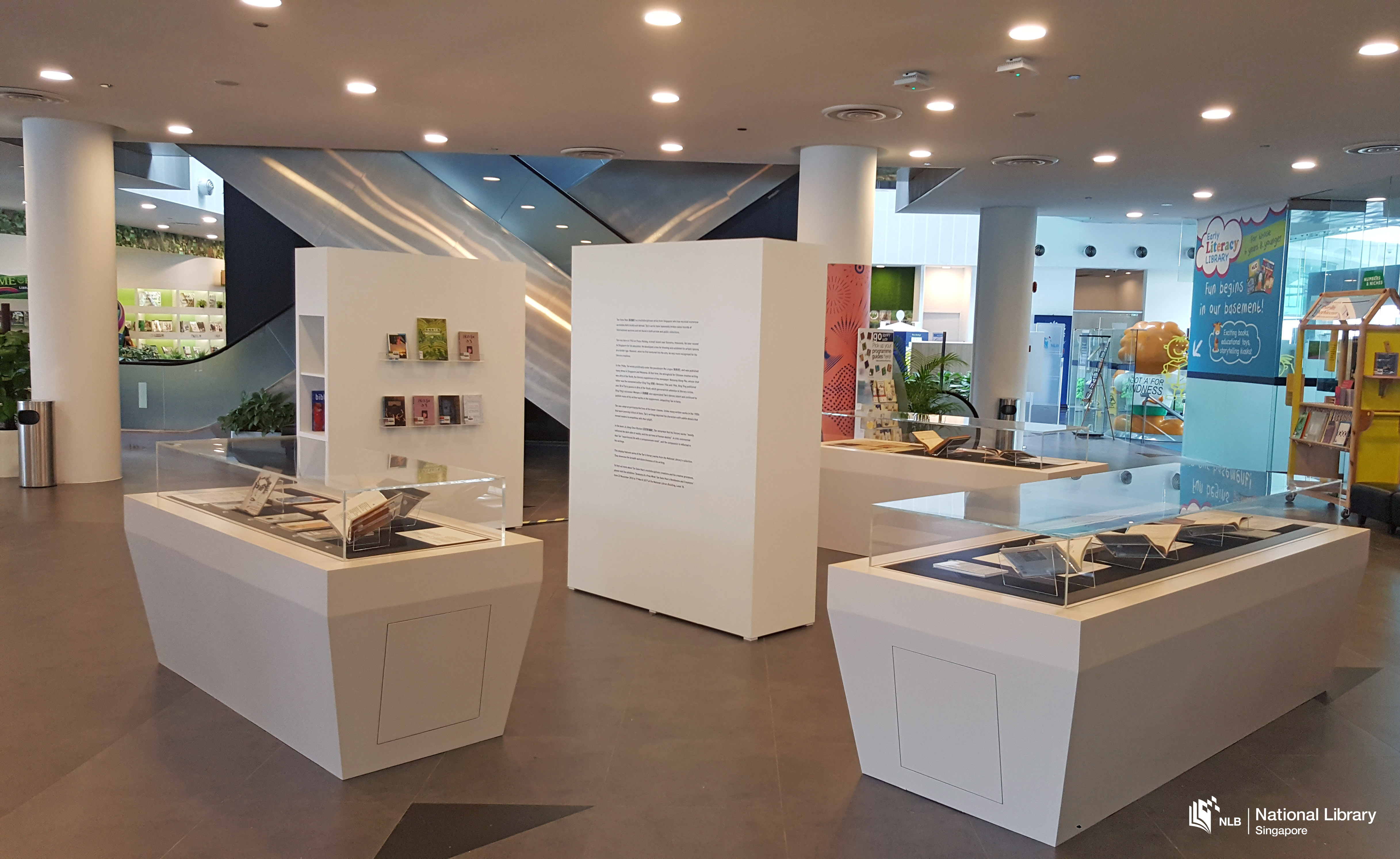 A photo of the roving exhibition. An information wall in the middle is surrounded by showcases and a wall with books.
