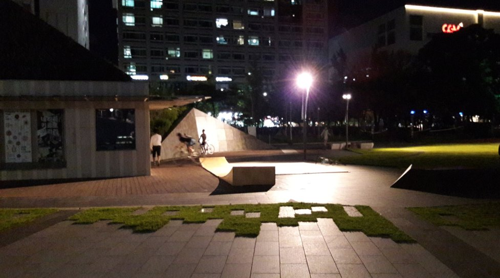 A nighttime view of the ramps at Buk Seoul museum site, with three young adults riding the ramps after hours.