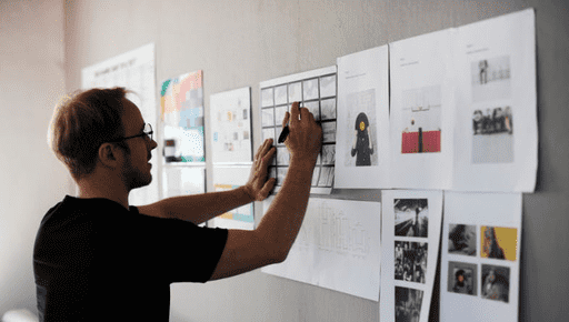 A man in glasses puts paper graphics and infographics and charts and graphs on a wall to show 13 reasons why businesses need a business plan fro Futrli for growth and success