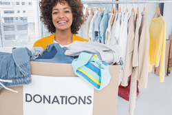 A person standing with a donations box filled with clothes.