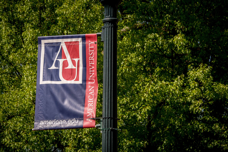 A campus flag hangs from a street light at American University