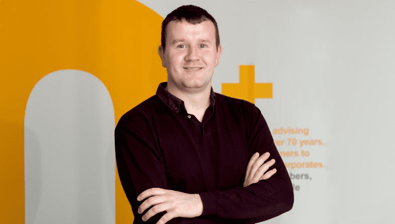 Sam King from advisory accounting firm Thorne Widgery in front of an orange logo.