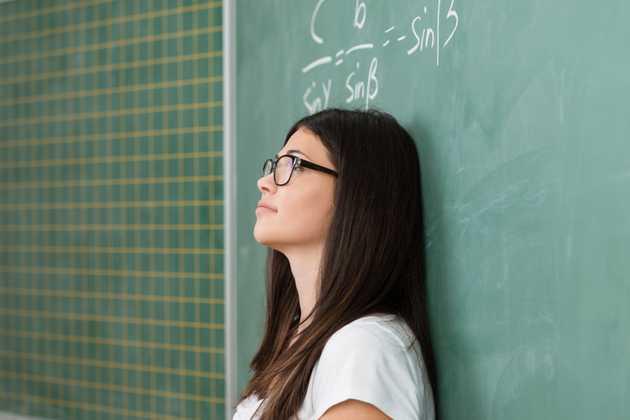 Woman leaning on blackboard