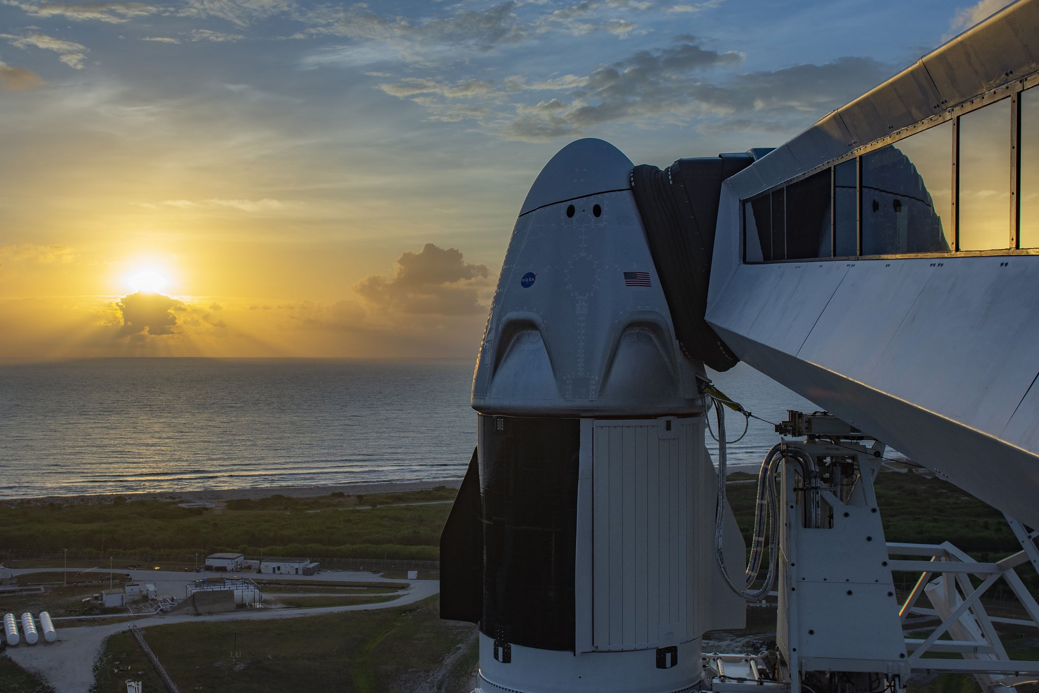 Imaginea 1: Capsula Dragon2 (sau Crew Dragon), așteptând o zi cu un cer mai senin, pe rampa de lansare LC-39A de la Kennedy Space Center. În drapta imaginii se poate observa brațul folosit pentru accesul echipajului la capsulă. (Sursa foto: SpaceX)