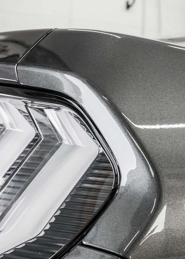 Close up of paint protection film (PPF) on rear light of grey Mustant GT car
