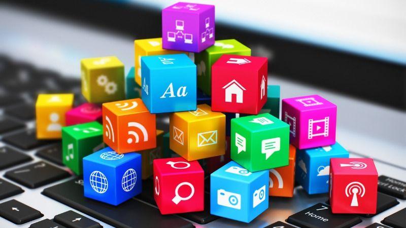 Auf einer Laptoptastatur liegt ein Haufen kleiner verschiedenfarbiger Würfel, die jeweils ein Symbol tragen, u.a. für Fotografie, Video, Chat, Text, Email, Audio, Internet und E-Mail.