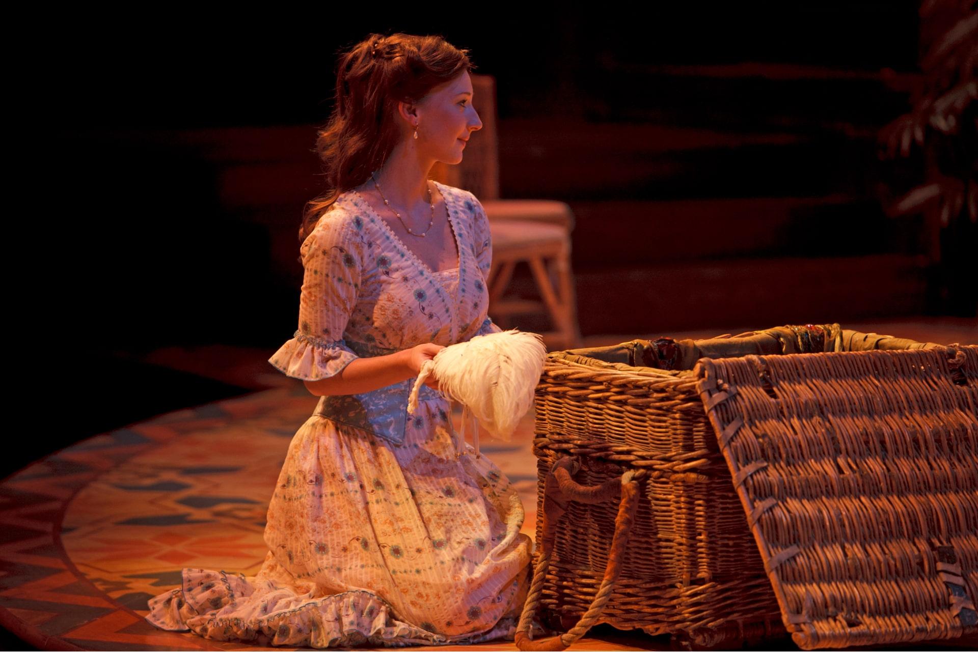 Kneeling woman unpacks wicker hamper bathed in warm sunlight,