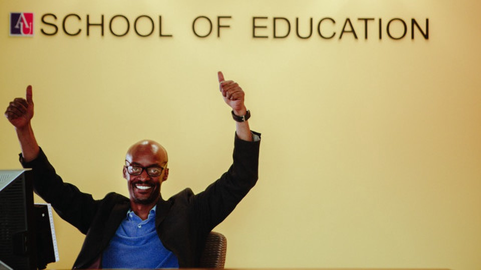 A man seated in front of a wall written School of Education. He has with both hands raised and is smiling.