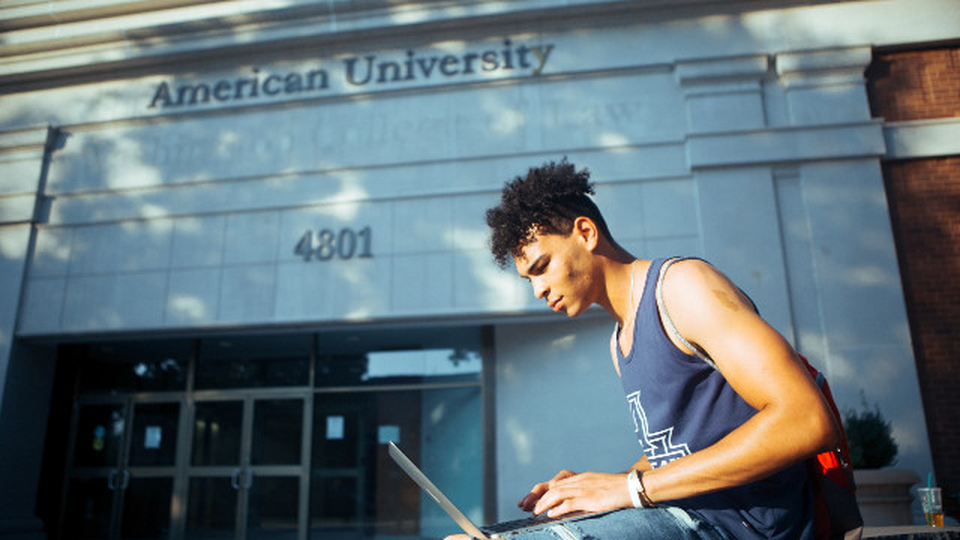 A man seated in front of an American University building typing something into a laptop