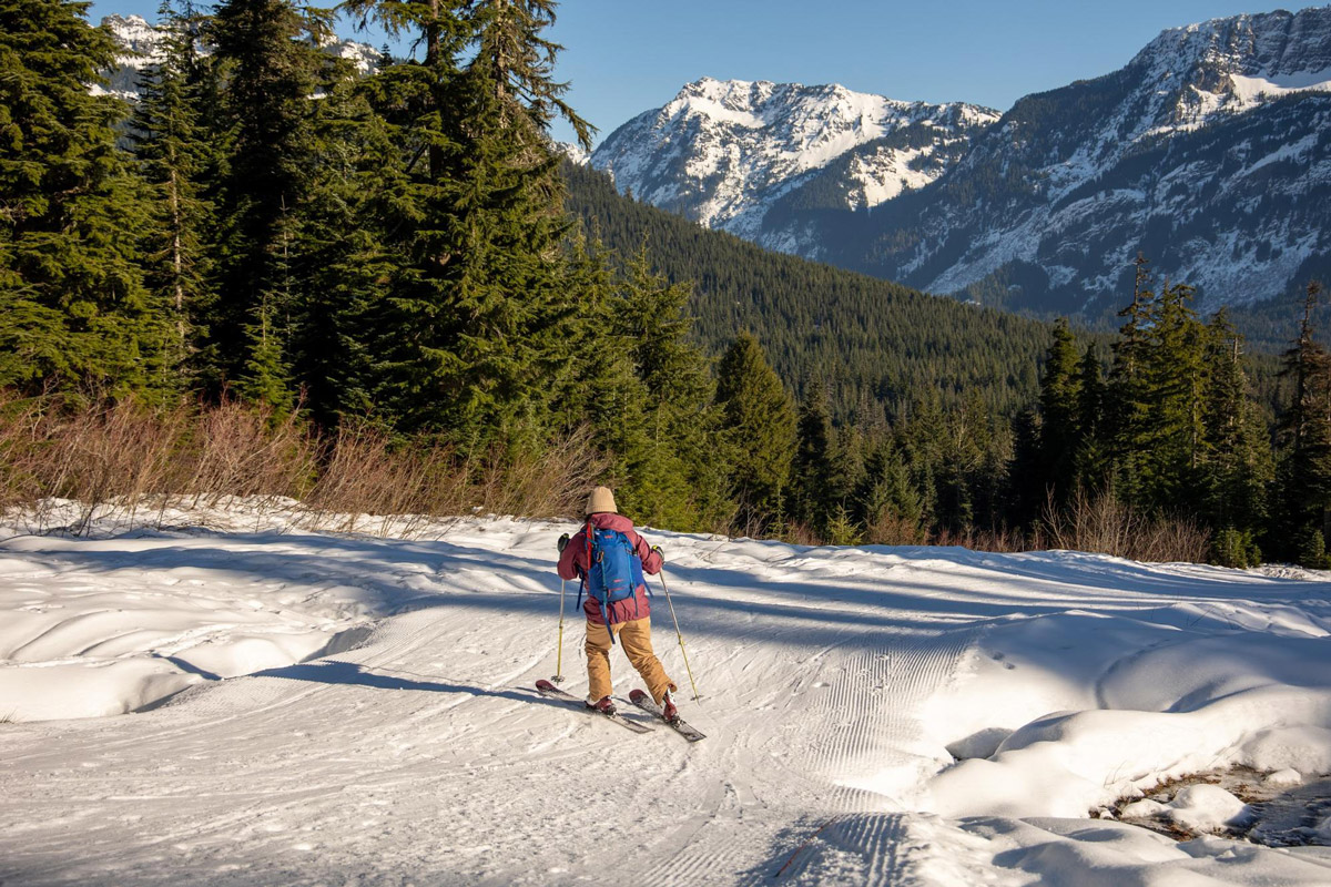Doris Wang skiing down a slop with a pine forest and snow-capped mountains in the distance.