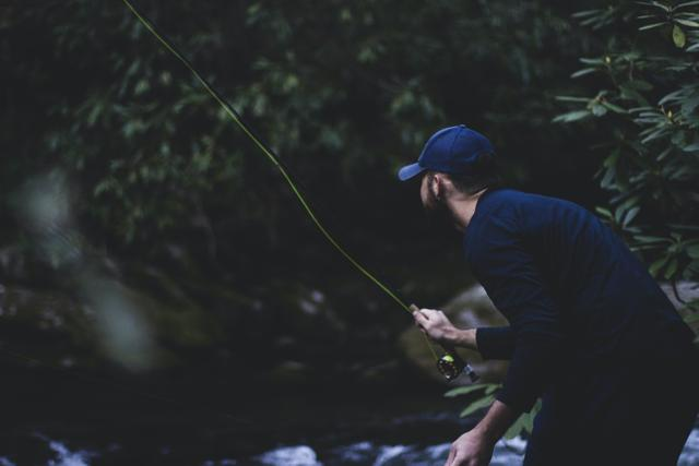 Shallow focus photography of man fly fishing