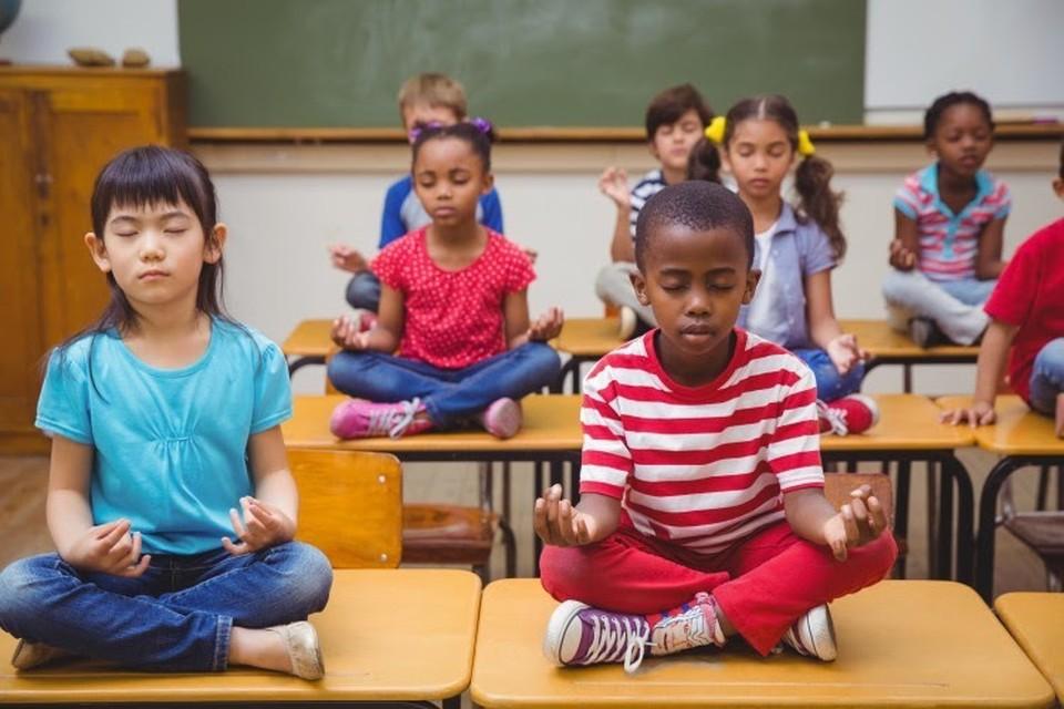 Students sit on desks while meditating.