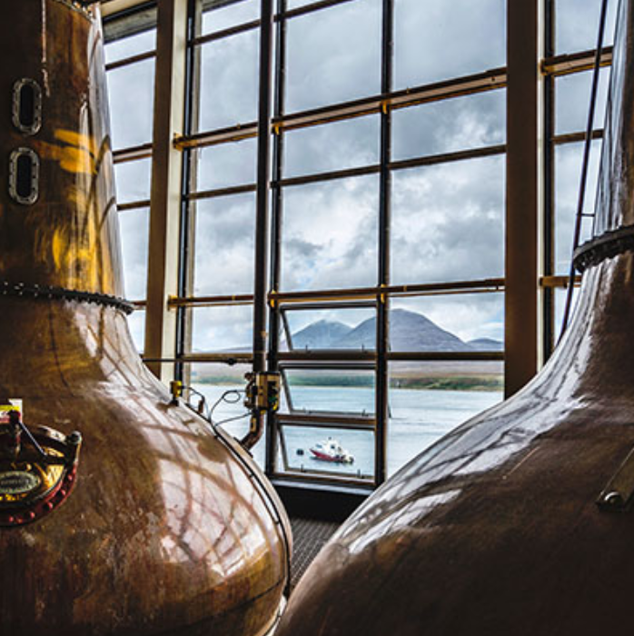 Caol Ila stills with a view of the Isle of Jura. Picture from: https://www.malts.com/en-row/distilleries/caol-ila/