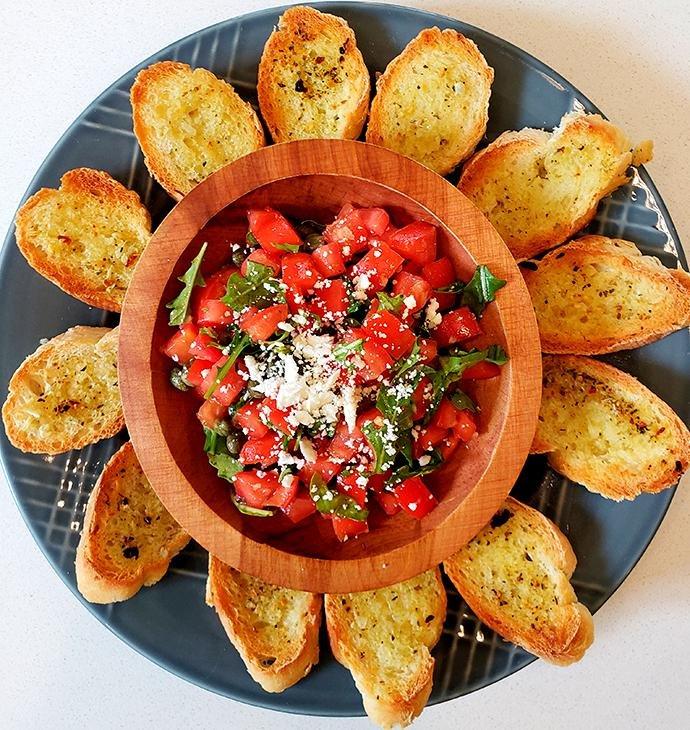 Plate with Mediterranean bruschetta served with baguette