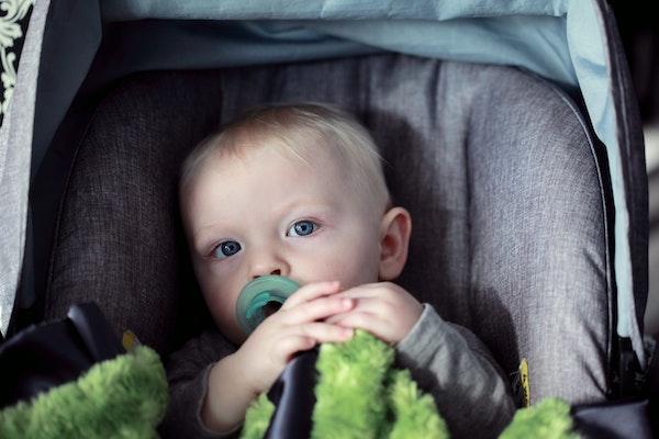 bebé en carrito con manta verde
