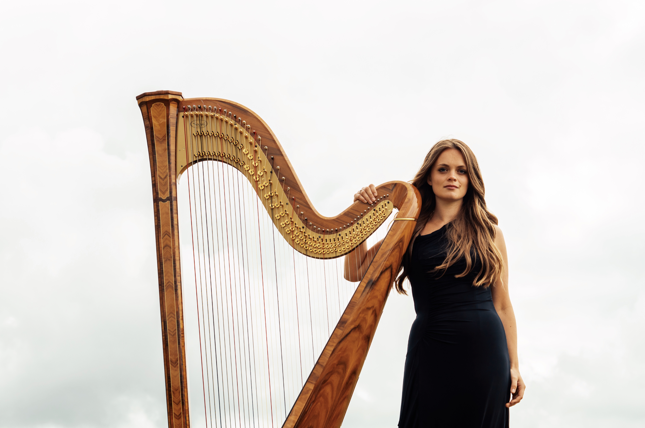 Dreamy photography by Jack Watkins against the clouds for award-winning classical musician and harpist, Lucy Nolan