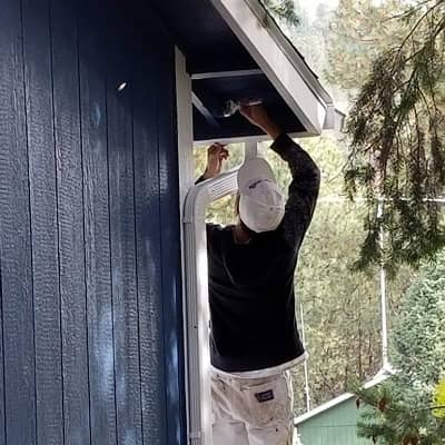 man painting the exterior of a home dark blue