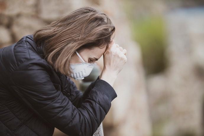 Stressed woman in mask. Photo: Engin Akyurt