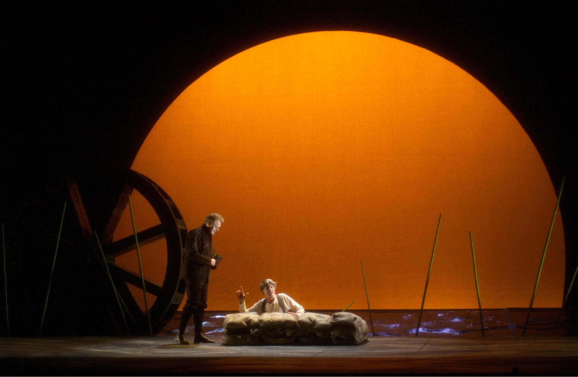 Man in black stands over man behind sandbags, against mill wheel and orange sunrise.